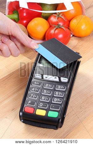 Using credit card reader payment terminal with contactless credit card and  fruits and vegetables in paper shopping bag cashless paying for shopping