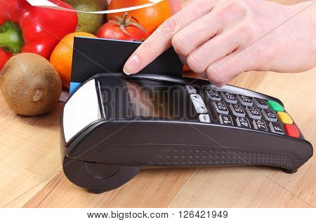 Using credit card reader payment terminal with credit card and fresh fruits and vegetables cashless paying for shopping
