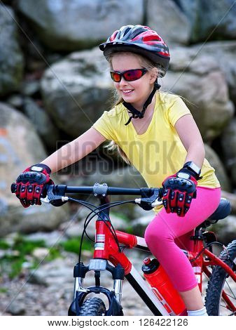 Bikes cycling girl into park. Girl rides bicycle into mountains.