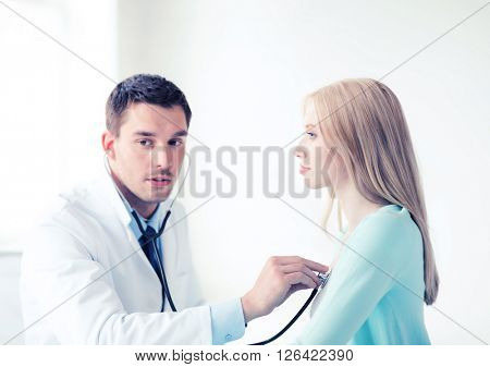 healthcare and medical - doctor with stethoscope listening to the patient in hospital