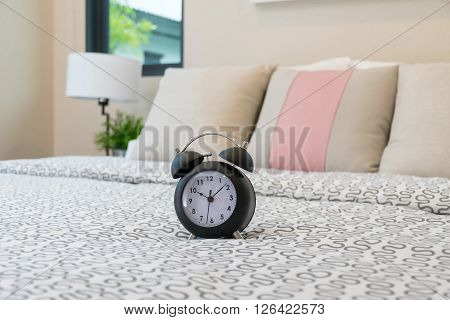 Close Up Of Alarm Clock On Bed In Bedroom