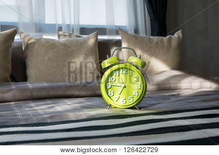 Modern Bedroom With Green Alarm Clock On Bed