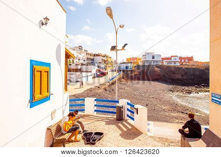 EL COTILLO, FUERTEVENTURA ISLAND, SPAIN - CIRCA JANUARY 2016: City street view with musicians playing on guitar in El Cotillo village on Fuerteventura island