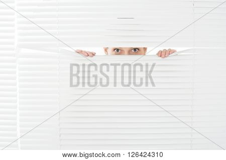 Young Woman Looks Through Jalousie