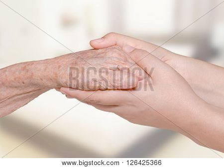Young woman's hand holding olderly's hand in bedroom