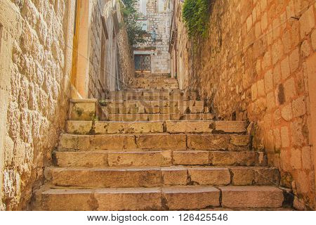 Narrow street and stairs in the Old Town in Dubrovnik, Croatia, Mediterranean ambient, warm filter, lens flare