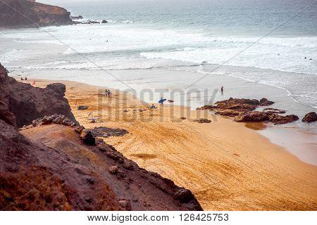 EL COTILLO, FUERTEVENTURA ISLAND, SPAIN - SIRCA JANUARY 2016: Top view on El Cotillo beach crowded with surfers. El Cotillo beach is very popular for surfing on Fuerteventura island