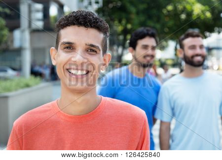 Laughing latin man with two friends in city