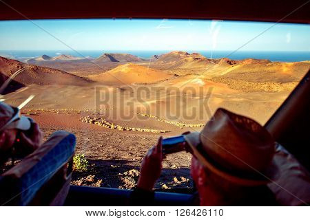 TIMANFAYA PARK, LANZAROTE ISLAND, SPAIN - SIRCA JANUARY 2016: Man makes pictures of volcanic landscape during bus excursion in Timanfaya park. Timanfaya park is entirely made up of volcanic soil