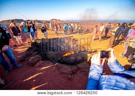 TIMANFAYA PARK, LANZAROTE ISLAND, SPAIN - SIRCA JANUARY 2016: Tourits near volcanic heating system in Timanfaya park. This park is entirely made up of volcanic soil and was designed by Cesar Manrique