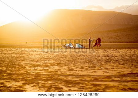 JANDIA, FUERTEVENTURA ISLAND, SPAIN - SIRCA JANUARY 2016: Couple windsurfers after the training on Sotavento beach on the sunset. Fuerteventura island is very popular island for surfing