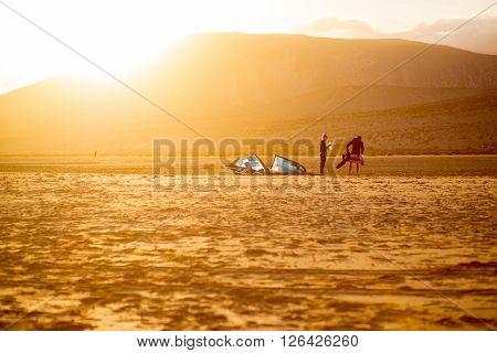 JANDIA, FUERTEVENTURA ISLAND, SPAIN - SIRCA JANUARY 2016: Couple windsurfers after the training on Sotavento beach on the sunset. Fuerteventura island is very popular island for surfing
