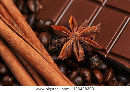 Coffee beans, bar of chocolate, cinnamon and star anise on the wooden table