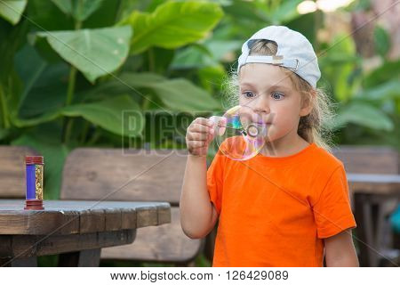 Little Girl In A Bright T-shirt Inflates Large Bubble In The Street