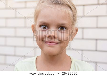 Portrait Of A Smiling Girl Six Years Against A Background Of A Brick Wall