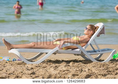 Young Tanned Woman Sunbathing On A Sun Lounger On The Beach Against The Backdrop Of People Bathing