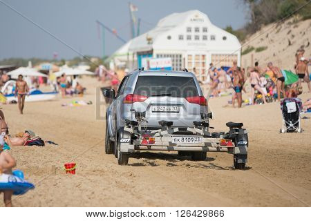 Anapa Russia - September 20 2015: passenger car with a trailer riding on the beach with holidaymakers