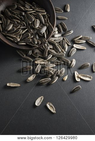 Sunflower seeds spilling out from a bowl.