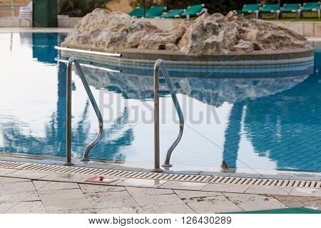 Metal handhold entrance to the blue hotel pool with stone island in a middle of the pool with reflection in water