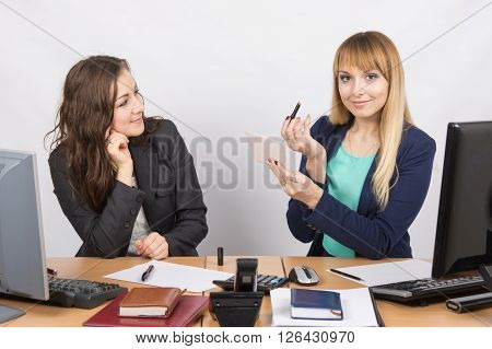 Office Employee At His Desk Looking At His Colleague, Who Is Holding Lipstick And Mirror In Hand