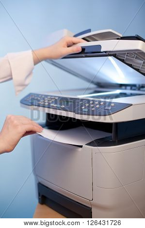 Woman's hand with working copier at office
