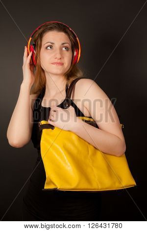 Picture of beautiful woman with headphones and handbag looking up