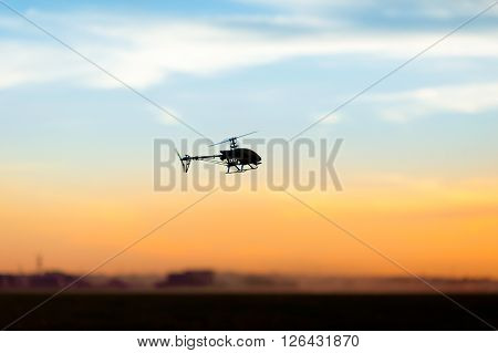 Photo of an RC copter flying at sunset