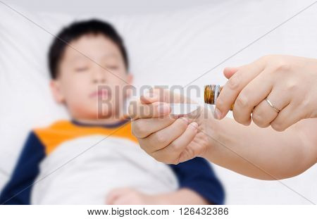 Mother's hand pouring syrup medicine for her sick child