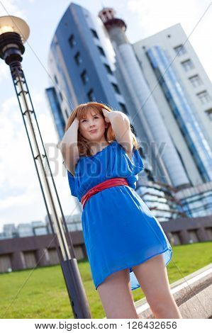 Beautiful ginger woman in blue dress and red belt against building