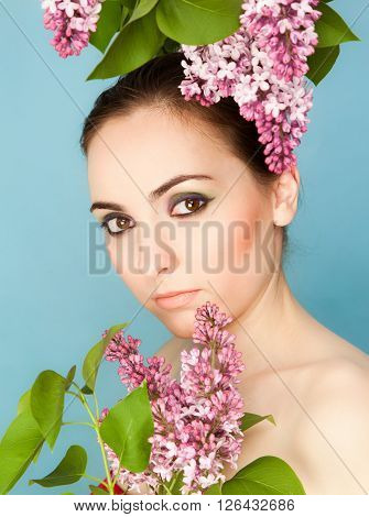 Portrait of beautiful woman with makeup and branch of lilac on blue background