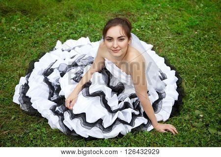 Picture of beautiful bride in white and black wedding dress lying on the grass
