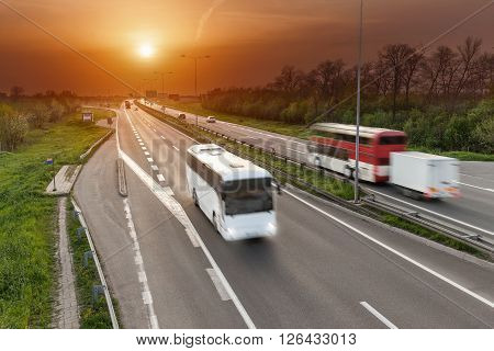 Two buses driving in motion blur on the freeway at beautiful sunset. Transport and travel scene on the motorway near Belgrade Serbia.