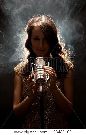 Picture of beautiful singer in gold dress with studio microphone