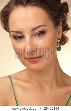 Portrait of beautiful woman with green earrings looking down