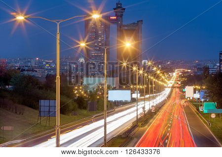 Blue hour shot of speed drive on freeway at the entrance to Belgrade Serbia with a view to the West Towers - west gate in the background. Llight trails at rush hour on motorway in long exposure shot.