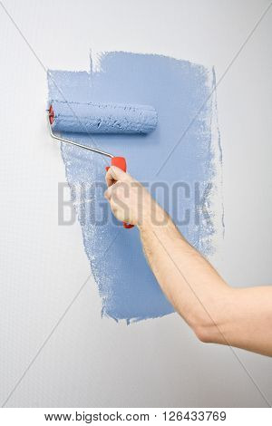 Picture of a hand painting the wall with roller