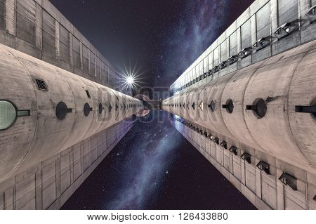 Upward view on twin towers known as the western gate of Belgrade in the sci-fi atmosphere with stars and milky way on the sky.