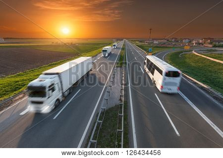 Many white trucks in line and fast travel bus driving towards the sun. Speed blurred motion drive on the freeway at beautiful sunset. Transport travel scene on the motorway near Belgrade Serbia.