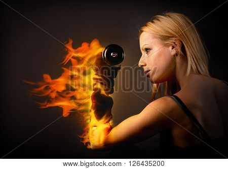 Woman lifting a weight on fire over dark background