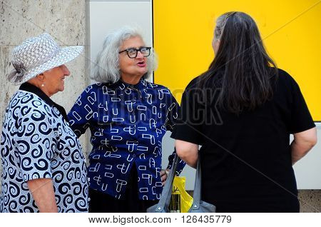 TRYAVNA, BULGARIA - JULY 6, 2015: Three elderly Caucasian women talk in the street of the town