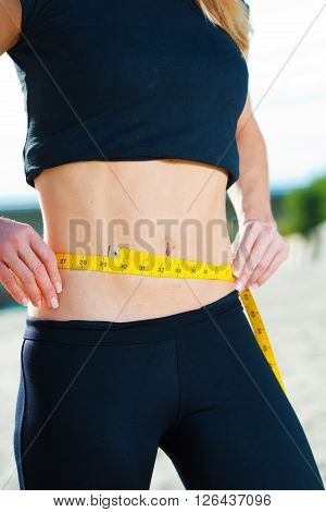 Fit woman measuring her waist outdoors with measuring tape