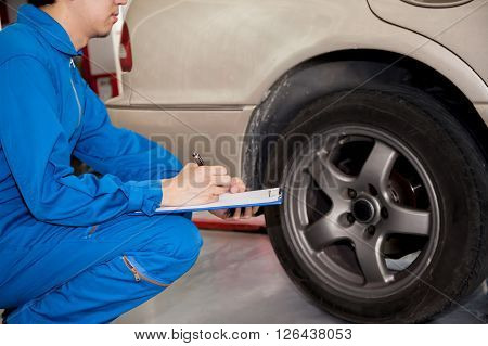 Young Automotive Technician Checking On Car Tires In Garage