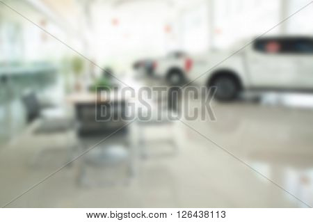 Blurred Of Inside Car Showroom With Chairs And Cars For Background