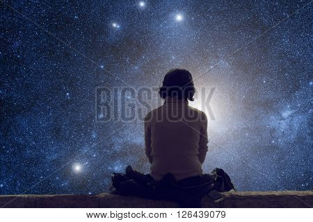 Silhouette of a lonely woman while watching the stars and Milky Way at night.
