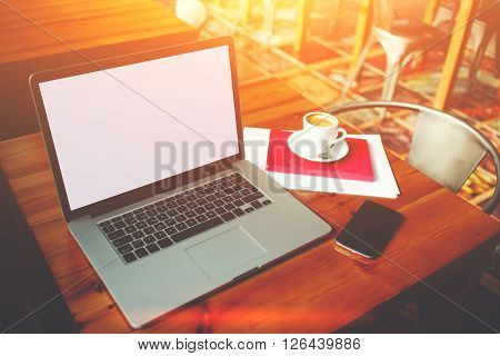 Open laptop computer and mobile phone with blank copy space screen for your information content or text message portable net-book with cell telephone lying on a wooden table in modern coffee shop