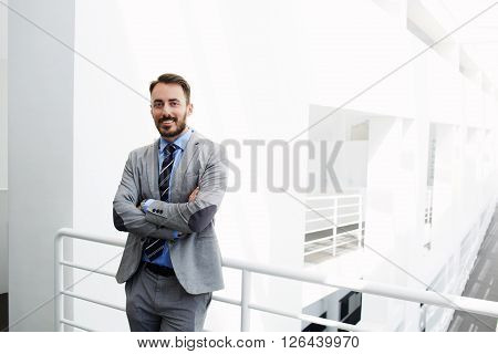 Smiling man government worker dressed in luxury suit is standing in modern interior during work break near copy space for your advertising text message or content. Happy male CEO is looking at camera