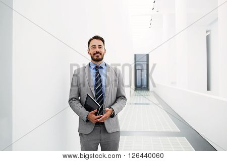 Smiling man employer with digital tablet in hands is posing before meeting with his staff while is standing in hallway enterprise with copy space for advertising text message or promotional content
