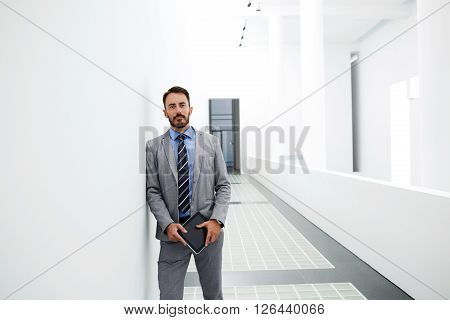 Man skilled economist is holding touch pad while is standing in modern interior near copy space for your advertising content. Male government worker with digital tablet in hands is looking at camera