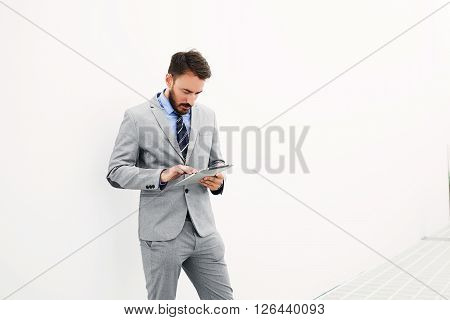 Man successful economist is searching in internet via touch pad needed for conference information while is standing in office interior near copy space for your advertising text message or content