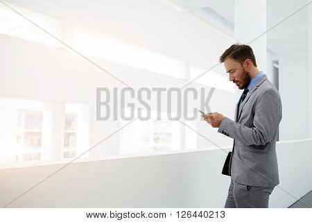 Worried businessman is reading e-mail on mobile phone from investor about suppression of the financing of his project while is standing in office interior near copy space for your advertising content